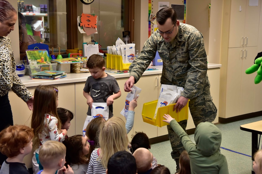 U.S. Air Force Capt. Glen Myers, a 354th Medical Group Dental Flight general dentist, hands out gift bags at the child development center on Eielson Air Force Base, Alaska, Feb. 11, 2020.