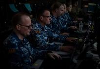 Royal Australian Air Force (RAAF) members look at computer screens.