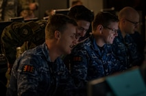 A U.S Air Force Airman and Royal Australian Air Force members look at a computer screen.