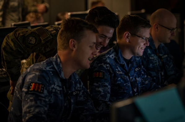 A U.S Air Force Airman and Royal Australian Air Force members look at a computer screen.