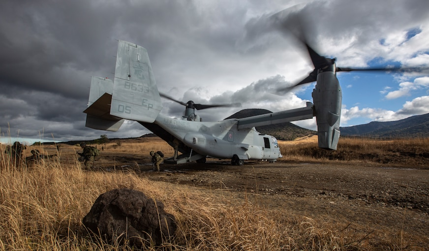 A Marine aircraft sits in an open field as service members exit.