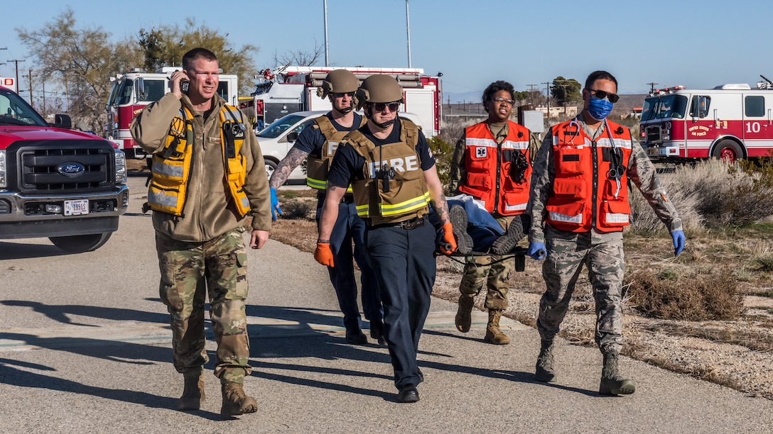 Fire and medical crews carry a victim towards a Los Angeles County Fire Department helicopter during an active shooter exercise at Edwards Air Force Base, California, Feb. 11. The victims were transported to the Antelope Valley Hospital in nearby Lancaster, California. (Air Force photo by Richard Gonzales)