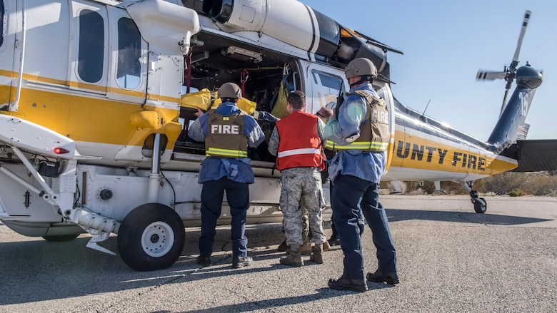 Fire and medical response crews load a victim onboard a Los Angeles County Fire Department helicopter during an active shooter exercise at Edwards Air Force Base, California, Feb. 11. The victims were transported to the Antelope Valley Hospital in nearby Lancaster, California. (Air Force photo by Richard Gonzales)