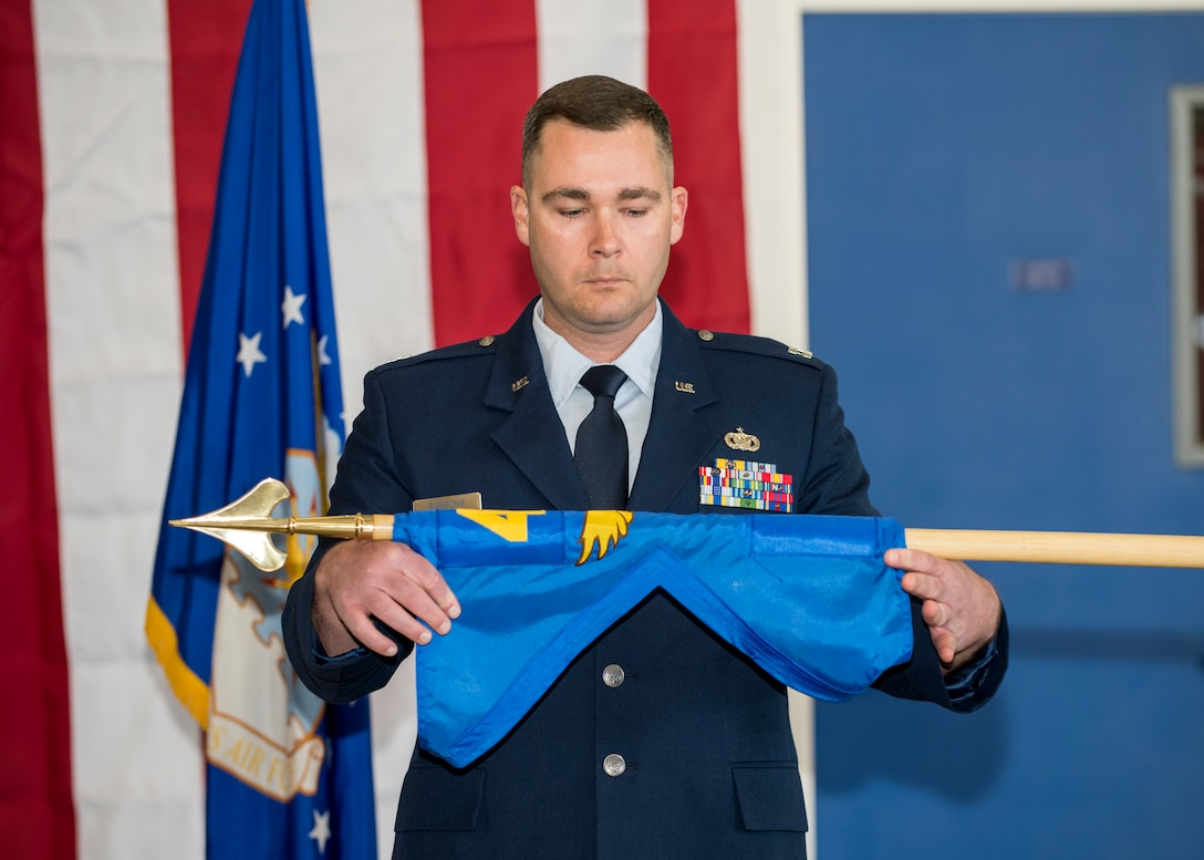 Capt. Daniel Parsons, 412th Security Forces Squadron Det. 1 Commander, unfurls his unit's guidon during an activation and assumption of command ceremony at the 412th Test Wing Operation Location Plant 42 in Palmdale, California, Feb. 13. (Air Force photo by Giancarlo Casem)