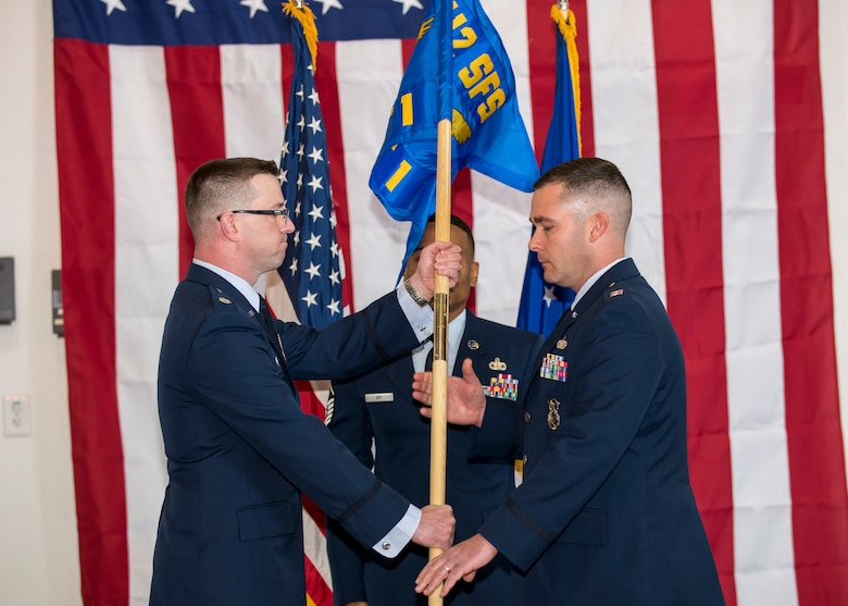 Lt. Col. Joseph Bincarousky, 412th Security Forces Squadron Commander, hands Detachment 1's guidon to Capt. Daniel Parsons signifying his assumption of command and activation of the unit at 412th Test Wing Operation Location Plant 42 in Palmdale, California, Feb. 13. (Air Force photo by Giancarlo Casem)