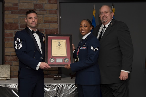 Senior Airman Troy Hicks, Airman Leadership School graduate, accepts the distinguished graduate award during the graduation of ALS class 20-2, Feb.13, 2020, on Holloman Air Force Base, N.M. The distinguished graduate award is presented to the top ten-percent of graduates for their performance in academic evaluations and demonstration of leadership. (U.S. Air Force photo by Airman 1st Class Kristin Weathersby).