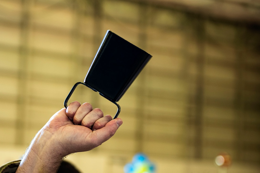 An Airman with the 23d Medical Group rings a cowbell in celebration during the Annual Awards Ceremony Feb. 14, 2020, at Moody Air Force Base, Georgia. The ceremony recognized the top military and civilian personnel in 10 separate categories. (U.S. Air Force photo by Senior Airman Erick Requadt)