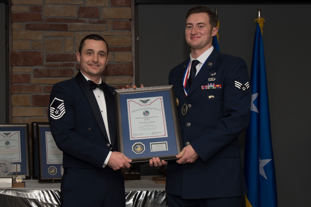 Senior Airman Troy Hicks, Airman Leadership School graduate, accepts the distinguished graduate award during the graduation of ALS class 20-2, February 13, 2020, on Holloman Air Force Base, N.M. The distinguished graduate award is presented to the top ten-percent of graduates for their performance in academic evaluations and demonstration of leadership. (U.S. Air Force photo by Airman 1st Class Kristin Weathersby).