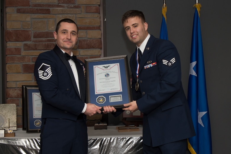Senior Airman Desmond Padilla, Airman Leadership School graduate, accepts the distinguished graduate award during the graduation of ALS class 20-2, February 13, 2020, on Holloman Air Force Base, N.M. The distinguished graduate award is presented to the top ten-percent of graduates for their performance in academic evaluations and demonstration of leadership. (U.S. Air Force photo by Airman 1st Class Kristin Weathersby).