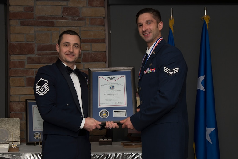 Senior Airman Daulton Charles, Airman Leadership School graduate, accepts the distinguished graduate award during the graduation of ALS class 20-2, February 13, 2020, on Holloman Air Force Base, N.M. The distinguished graduate award is presented to the top ten-percent of graduates for their performance in academic evaluations and demonstration of leadership. (U.S. Air Force photo by Airman 1st Class Kristin Weathersby).