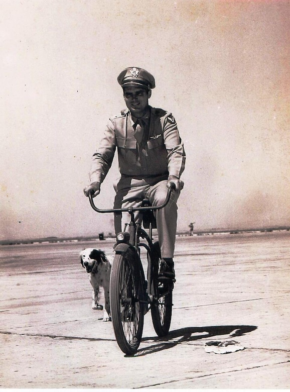 Brig. Gen. Robert Travis, 9th Heavy Bombardment Wing commander, rides his bike to work followed by his dog, Dan, at Fairfield-Suisun Air Force Base, California. Travis was killed when his B-29 Superfortress crashed Aug. 5, 1950. The base was renamed in his honor one year later. (U.S. Air Force photo)
