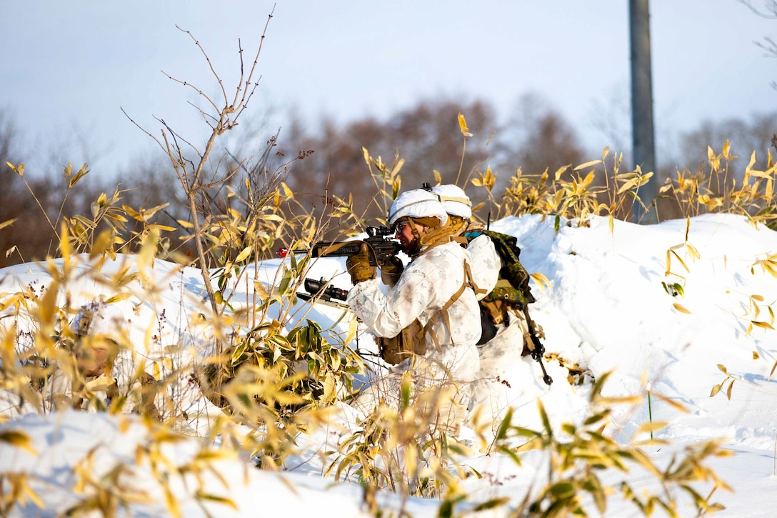 Two Marines kneel down in snow holding weapons.