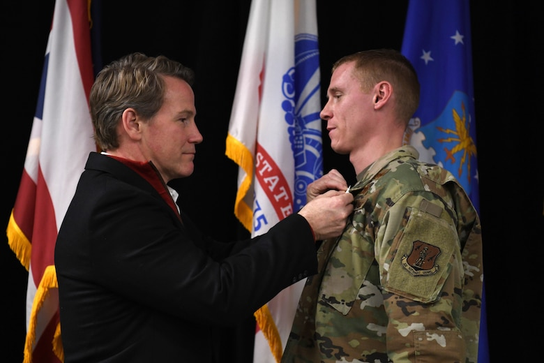 Ohio's Lt. Governor Jon Husted awards the Ohio Cross to U.S. Air Force Master Sgt. Ryan Tucker during the Ohio National Guard's Joint Senior Leaders Conference Feb. 14, 2020 in Columbus, Ohio. The Ohio Cross is awarded to any member of the state military forces who distinguishes themselves by gallantry and intrepidity at the risk of their life. (U.S. Air Force photo by Tech. Sgt. Shane Hughes)