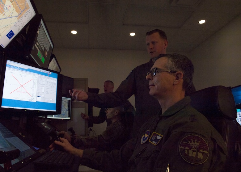 Maj. Gen. Craig D. Wills, 19th Air Force commander, flies an MQ-9 simulator with direction from Capt. Christopher, 6th Attack Squadron flight commander, Feb. 13, 2020, on Holloman Air Force Base, N.M. The 16th Attack Squadron uses MQ-9 simulators to train pilots and sensor operators for their field. (U.S. Air Force photo by Airman 1st Class Autumn Vogt)