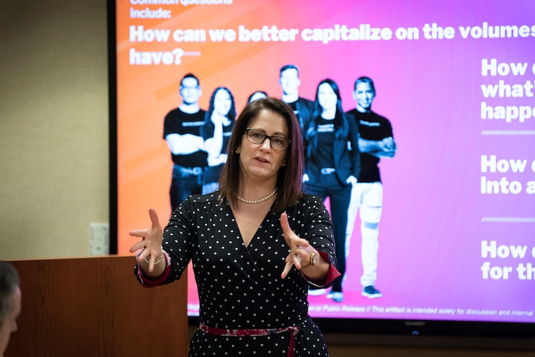 Woman standing in front of an illustrated briefing slide gestures with both hands while speaking.