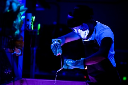 An airman wearing gloves and protective headgear works over a basin in a room illuminated by ultraviolet light.