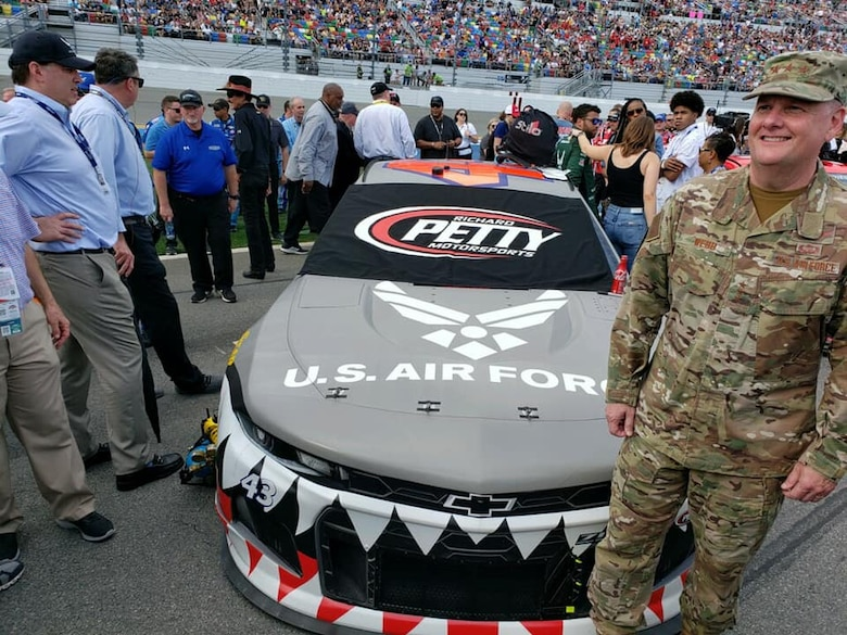 General Webb standing next to a race car