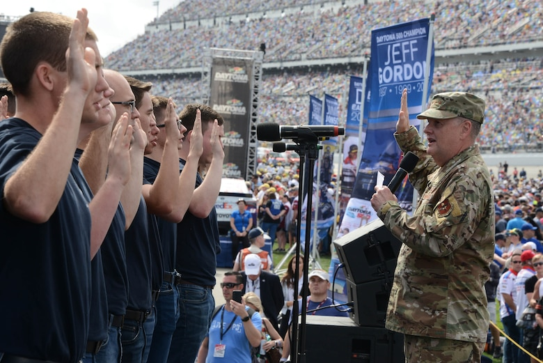 Lt. Gen. Brad Webb, Air Education and Training commander, conducts a Total Force mass oath of enlistment to 30 new members of the Air Force at the Daytona 500.