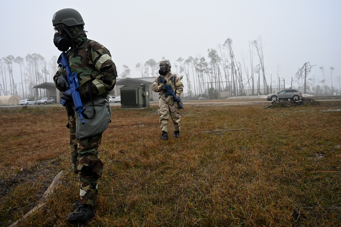 Airmen in chemical warfare gear patrolling with rifles.