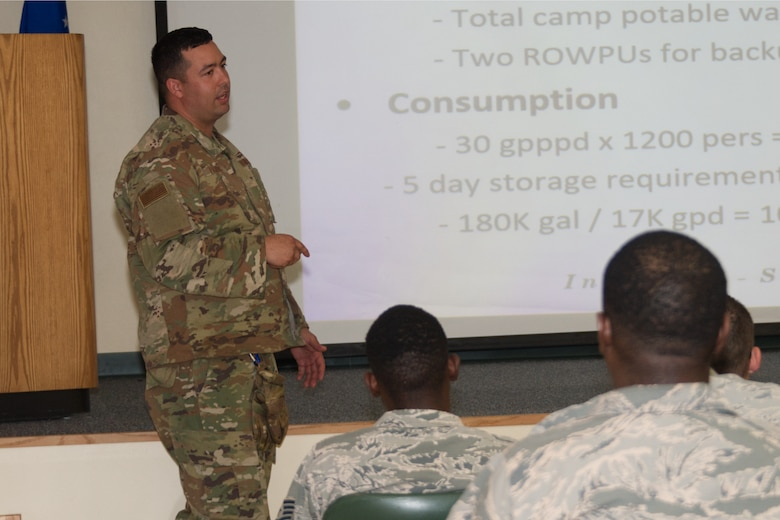 Photo of Airman delivering a briefing to crowd.