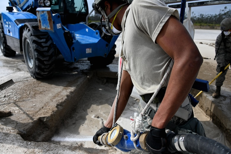 Photo of Airman adding water to concrete mix.
