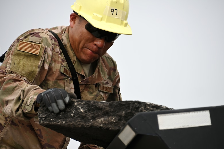 Photo of Airman moving asphalt.