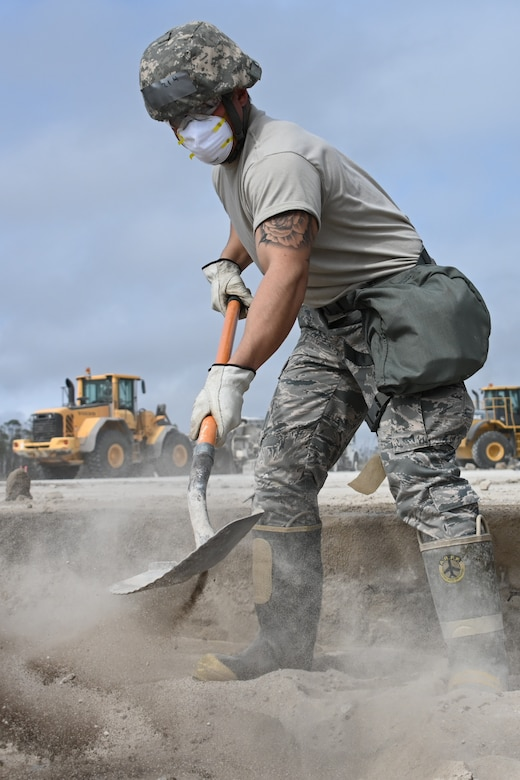 Photo of Airman shoveling concrete.