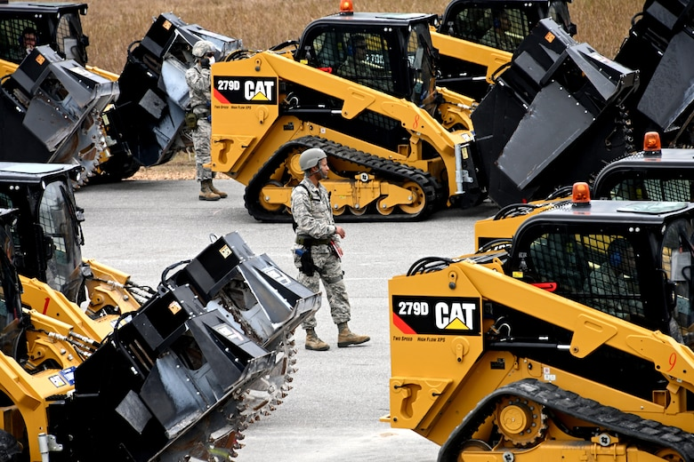 Photo of Airman walking among heavy equipment vehicles.