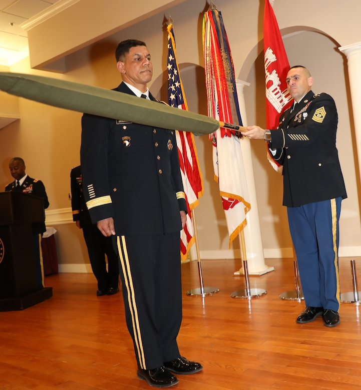 Transatlantic Division Command Sergeant Major Randolph Delapena assists Brig. Gen. Quander in uncasing and unfurling the one-star flag representative of an army brigadier general. All general officers are issued a flag embroidered in the center with their rank. The flag, when displayed, signifies a general's presence. Delapena's participation in the ceremony also represented the enlisted rank and signified the senior enlisted advisor as the keeper of the colors for military officers.