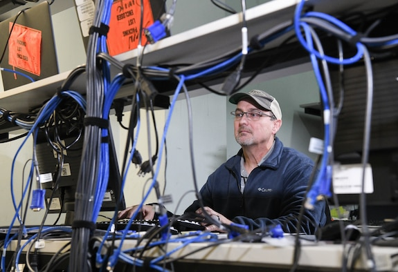 Troy Haywood, lead computer network technician, restages a computer for Non-Classified Internet Protocol Router Network, Dec. 12, 2019, in the PC Staging Area at Arnold Air Force Base, Tenn. Computers must be loaded with required software and necessary security protocols prior to being deployed for use by AEDC team members. (U.S. Air Force photo by Jill Pickett)