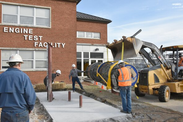 Workers with Henley Construction and Welding Unlimited install an F100 engine for display outside of the Engine Test Facility at Arnold Air Force Base. The installation of the display was completed in late 2019 and coincided with the 50th anniversary of the first operation at Arnold AFB involving the F100, which occurred on Dec. 18, 1969. Since then, Arnold Engineering Development Complex has logged over 23,000 hours testing the F100 series of engines in numerous test facilities. (U.S. Air Force photo by Bradley Hicks) (This image was altered by obscuring badges for security purposes.)