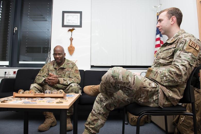 Photo of two Airmen conversing at a table