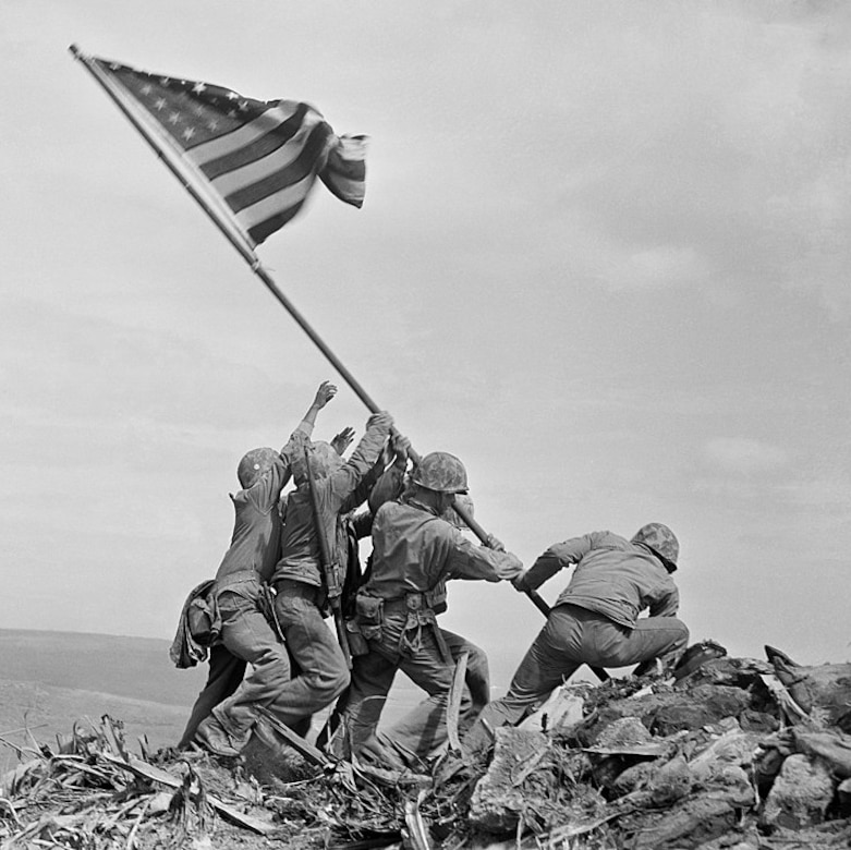 Black and white photo of Marines lifting an American flag to plant it on top of a mountain.