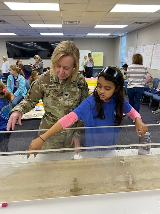 A girl scout shows Colonel Schlosser an engineering project.