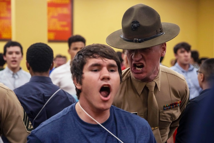 Staff Sgt. Leland Crecelius , a drill instructor with Receiving Company, Support Battalion, corrects a recruit with Golf Company, 2nd Recruit Training Battalion, during receiving at Marine Corps Recruit Depot, San Diego, Feb. 10, 2020