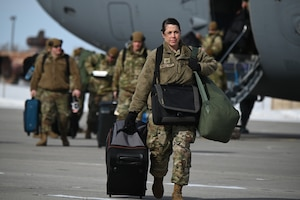 Photo of Master Sgt. Kari Appletoft with her luggage as she walks across the flight line upon returning on a C-17 aircraft from Exercise Southern Strike 20.