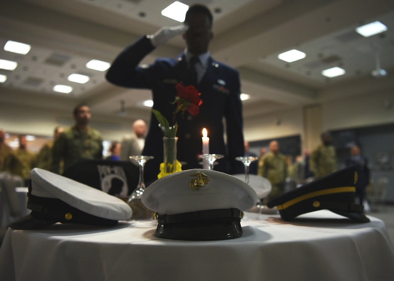 U.S. Air Force Senior Airman Ashley Louis, 17th Logistics Readiness Squadron deployment technician, salutes the POW/MIA table during the Airman Leadership School Graduation Ceremony in the event center at Goodfellow Air Force Base, Texas, Feb. 13, 2020.  Traditionally, ALS graduates set the POW/MIA table at the ceremony. (U.S. Air Force photo by Airman 1st Class Abbey Rieves)