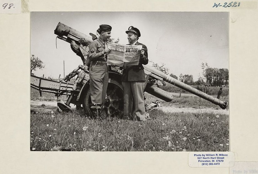 Two men stand by a large gun and hold a newspaper.