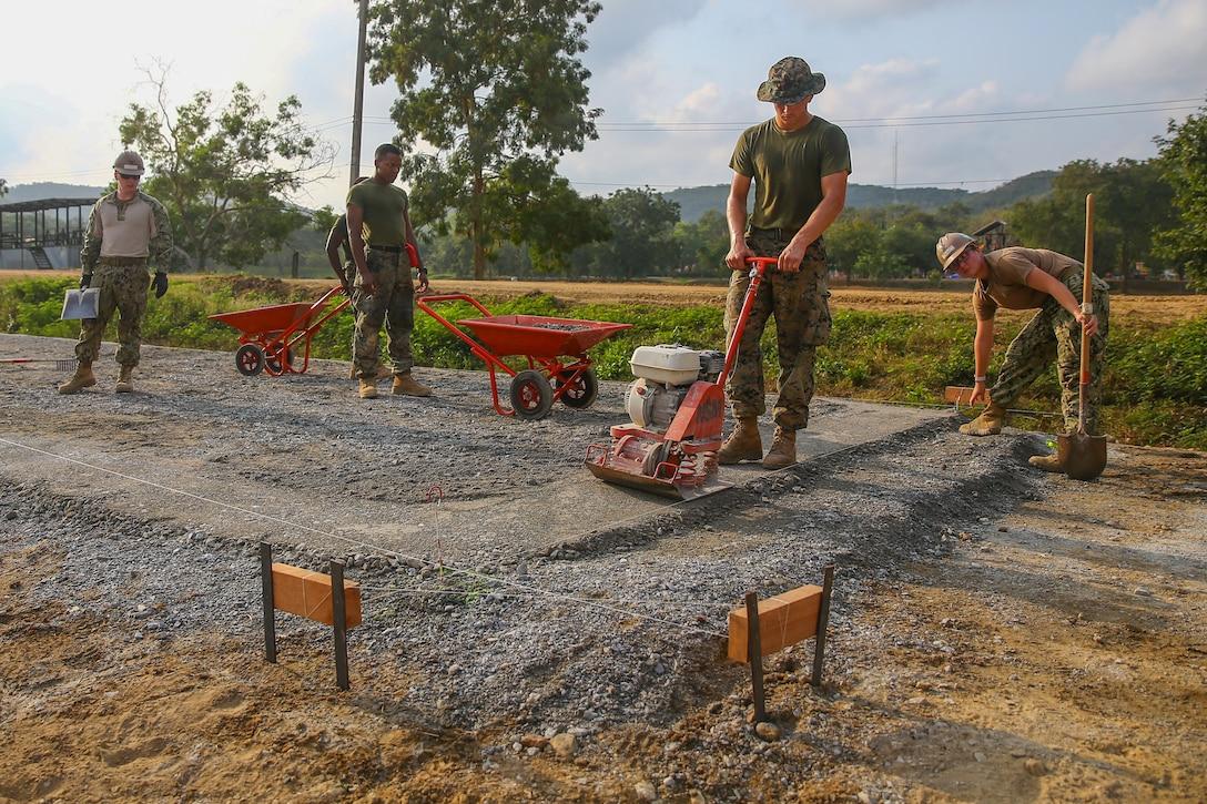 U.S. service members dump, spread and compact fresh gravel during a subject matter expert exchange on Royal Thai Marine Base Sattahip, Kingdom of Thailand, Jan. 23.