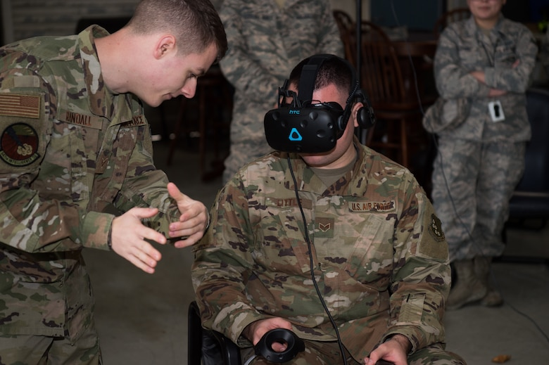 (Left) U.S. Air Force Senior Airman Ronald Randall, 547th Intelligence Squadron instructor, Nellis Air Force Base, Nevada, helps (right) Senior Airman Joshua Little, 1st Operations Support Squadron intel analyst, use a virtual reality system brought to Joint Base Langley-Eustis, Virginia, by Airmen from the 547th IS, Feb. 12, 2020.