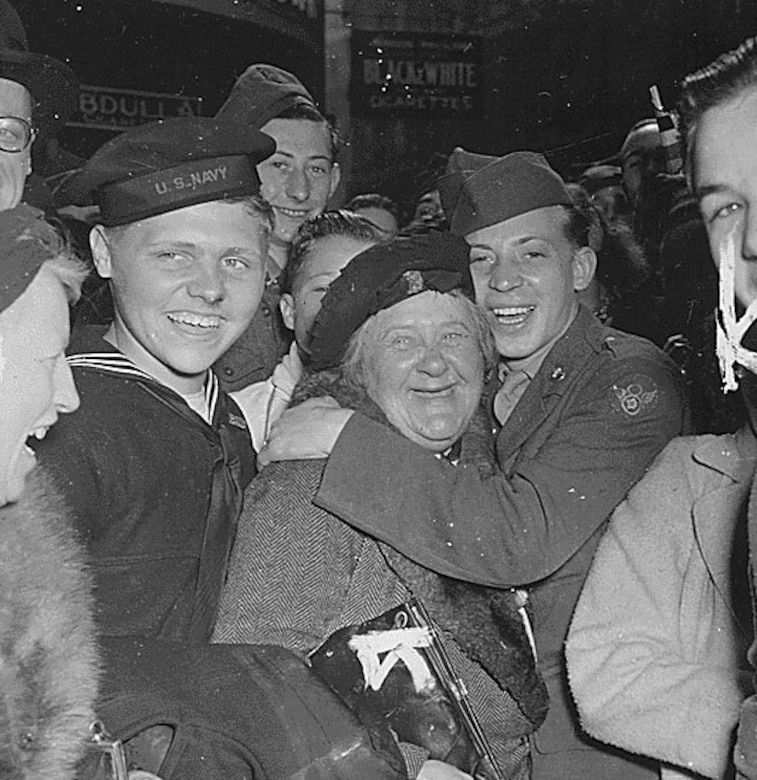 Soldiers, sailors and civilians hug each other and smile at the camera.