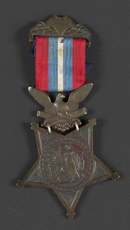 A star medal with an insignia is held to a clasp with a red, white and blue ribbon.