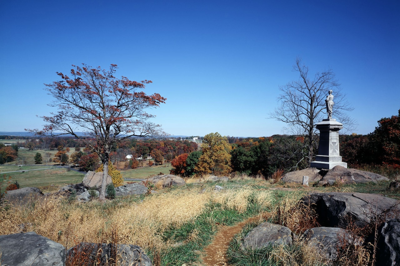 Rocks, autumn trees and brush cover a hillside. On the right is a monument with a man's statue on top.