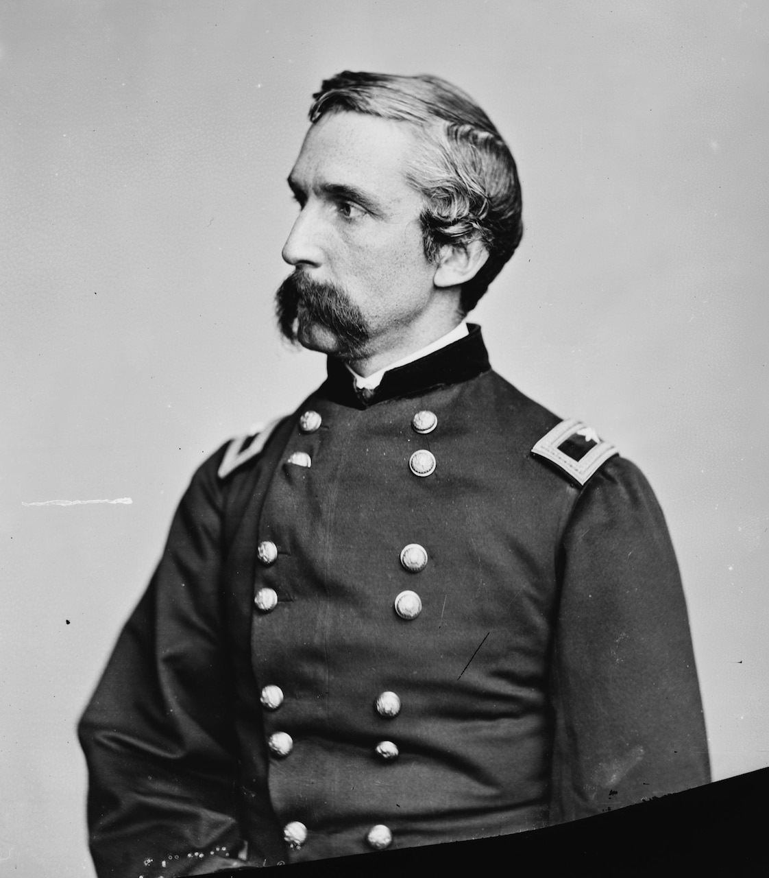 A man with a large mustache in Civil War dress uniform poses while looking into the distance.