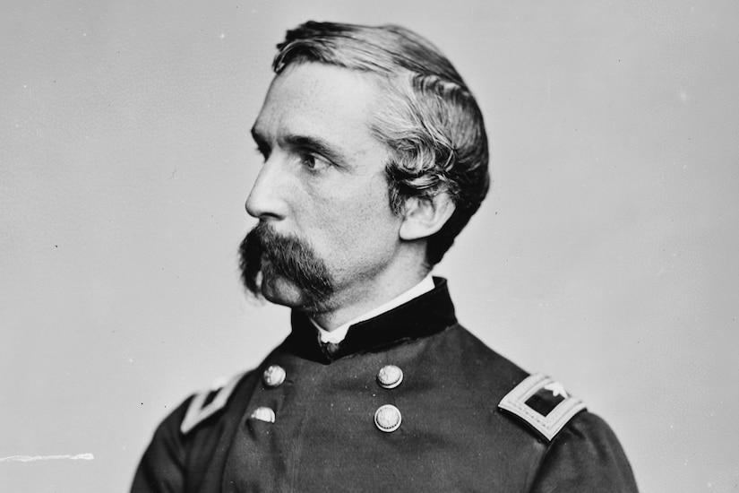 A man with a large mustache in a Civil War dress uniform poses while looking into the distance.