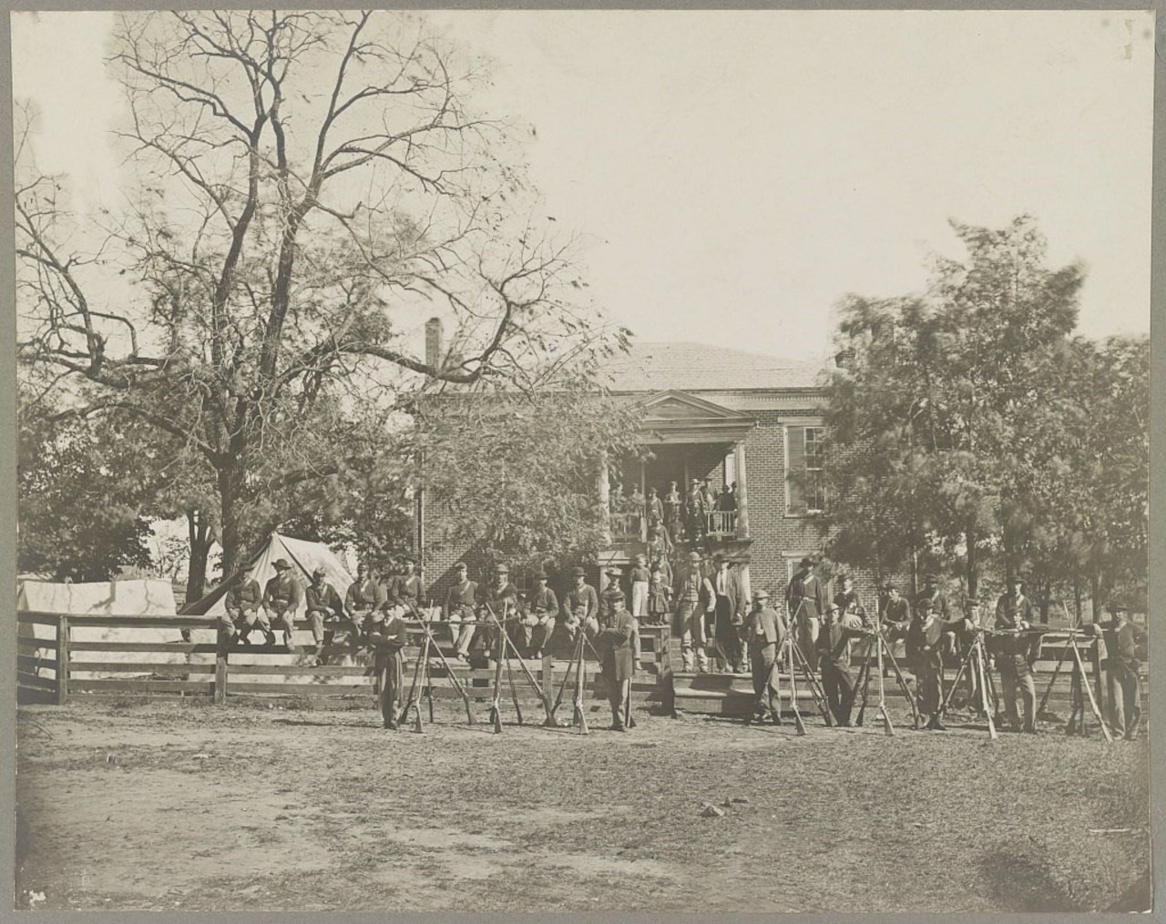 Dozens of Civil War soldiers holding muskets stand in front of a two-story building. More men sit on a fence, while others stand on a second-story balcony.