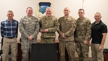 A group of military and civilian Airmen celebrate the wing's winning of the 2019 Air National Guard, Director of Safety Award for Outstanding Achievement in Occupational Safety by posing with the award.