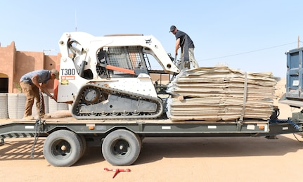 Photo of Airmen delivering protective barriers to help fortify a National Guard of Niger's compound.