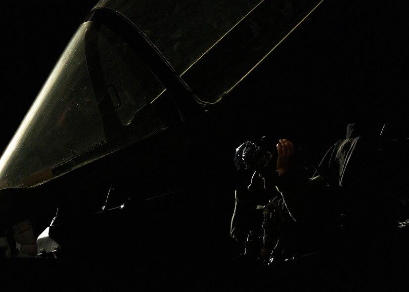 An F-35A Lightning II fighter jet pilot puts on his helmet.