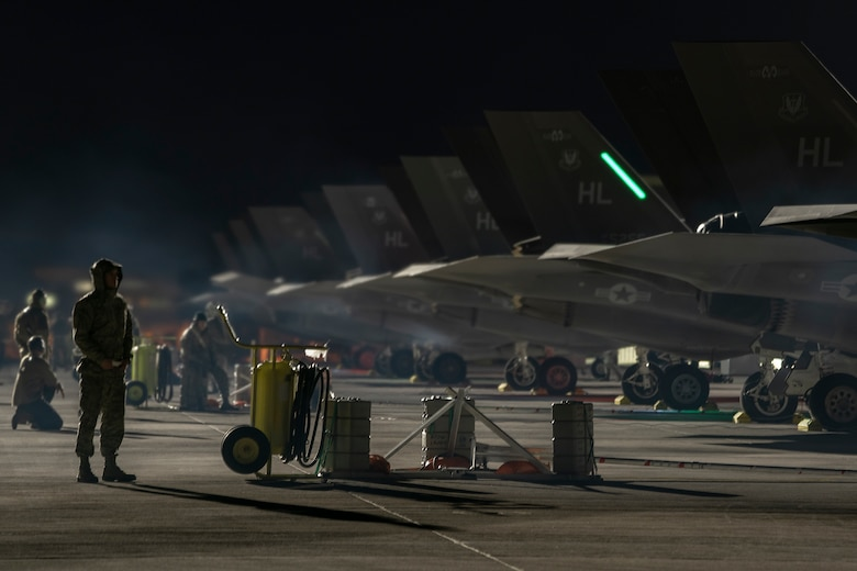 Airmen stand behind a row of F-35A Lightning II fighter jets at night.